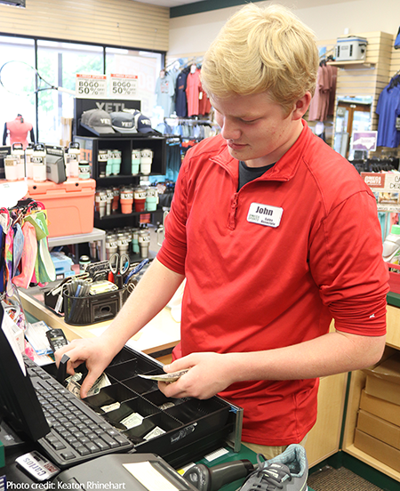 teen counting change at cash register