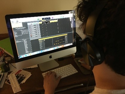 Teen using GarageBand on a computer to record music